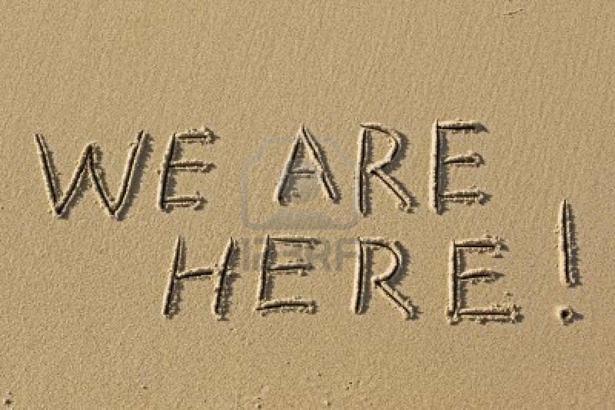 We Are Here written in sand